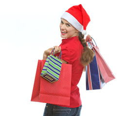 Young woman in Christmas hat with shopping bags looking out