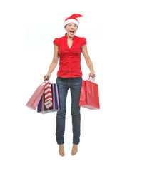 Happy young woman in Christmas hat with shopping bags jumping