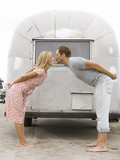 couple in front of their airstream classic trailer