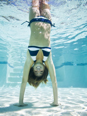 teenage girl doing a handstand under water