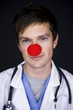 doctor wearing a red clown nose