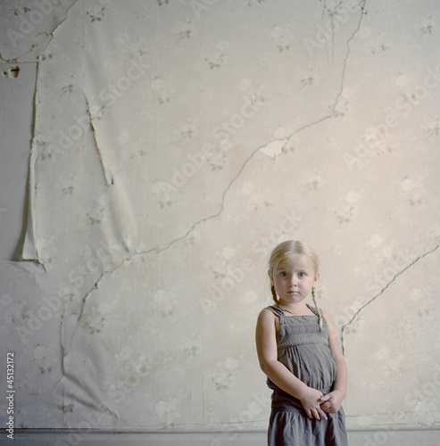 """USA, Montana, Bannack, Girl (2-3) posing against wall with peeling wallpaper"""