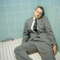 """""""USA, Utah, Salt Lake City, Mid adult man wearing suit lying down at corner"""""""