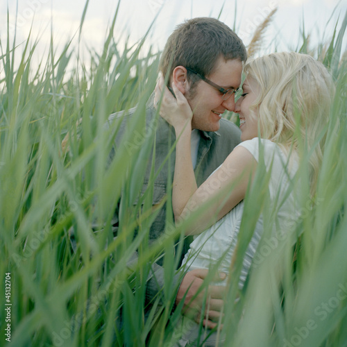 """USA, Utah, Salt Lake City, Young happy couple embracing, blades of grass in foreground"""