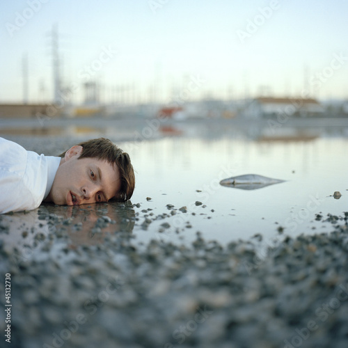 """USA, Utah, Salt Lake City, Dead man lying in puddle with dead fish"""