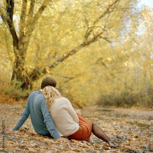 """USA, Utah, Salt Lake City, Young couple sitting together in autumn park, rear view"""