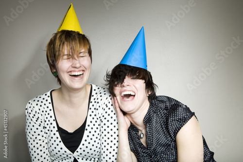 Studio shot of two women wearing party hats