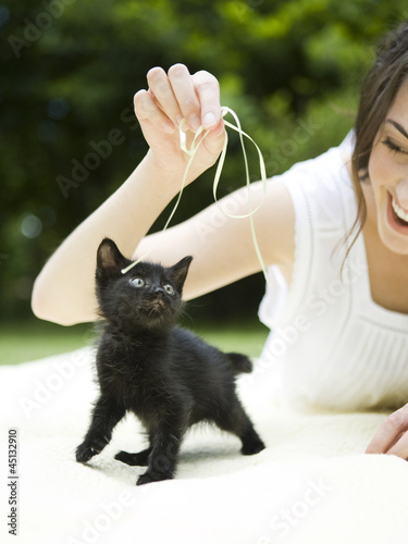 """USA, Utah, Orem, Woman playing with kitten"""