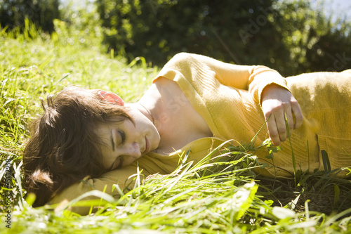 """USA, Utah, Orem, Woman relaxing on grass"""