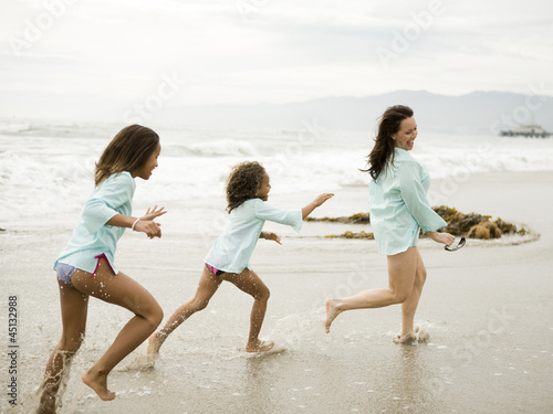 """USA, California, Los Angeles, Mother with daughters (6-11) running on beach"""