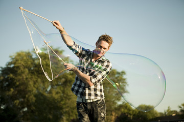 """USA, Utah, Orem, Man making large soap bubble"""