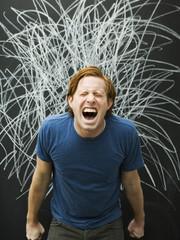 Studio shot of man yelling with chalk scribble on blackboard