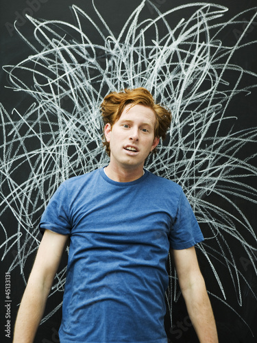 Studio portrait of man with chalk scribble on blackboard