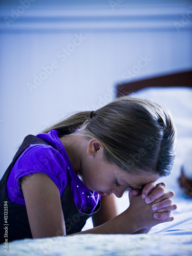 girl praying by her bed