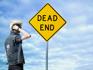 man looking at a dead end sign