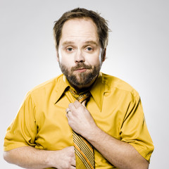man in a yellow shirt and tie fixing his tie