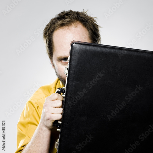 man hiding behind his briefcase