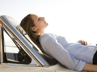 woman asleep on the hood of her car