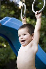 little boy hanging from a jungle gym