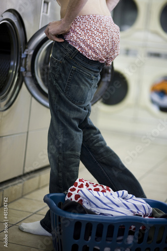 man putting on jeans at the laundromat