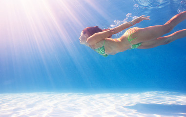 Woman swimming underwater in a blue pool.