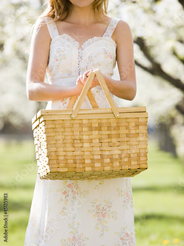 woman in a white dress holding a picnic basket