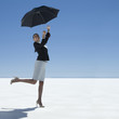 businesswoman holding an umbrella in the desert