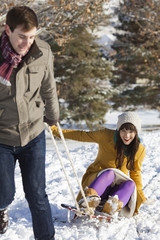 young couple sledding in the snow