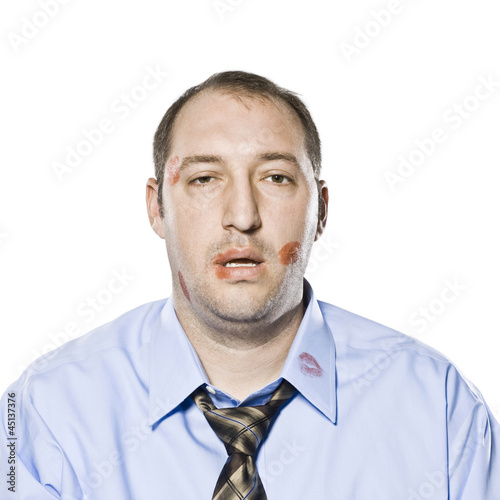 businessman with lipstick kiss marks all over his face