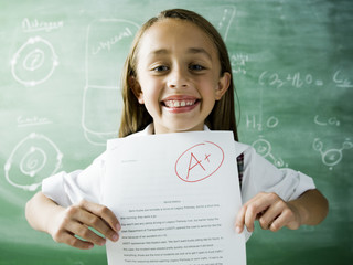 girl in a classroom holding up an a plus paper