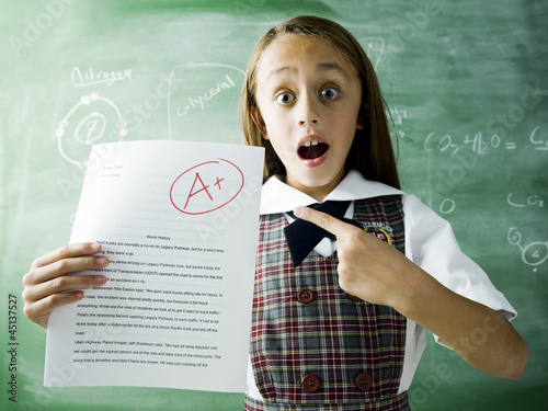girl in a classroom standing in front of a chalkboard with an a plus paper