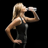 Young woman drinking water from bottle