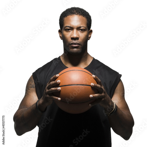 Portrait of male basketball player holding ball