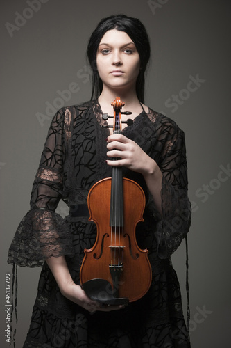 Studio portrait of young woman holding violin