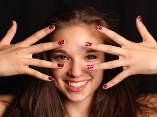 Mädchen lächelt durch Hände hindurch