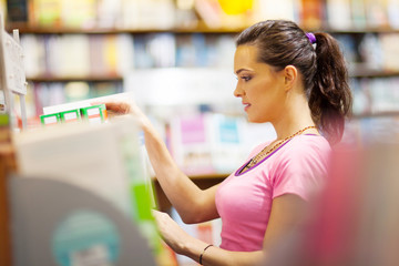 young woman choosing a book in bookstore or library