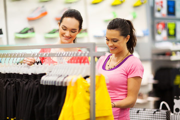 two young women shopping for clothes in sports shop