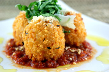 Risotto balls, fried golden brown with a spicy tomato sauce.