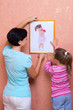 Woman with little girl hang up a picture