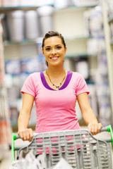 happy young woman pushing trolley in supermarket