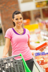 happy young woman shopping for frozen food in supermarket