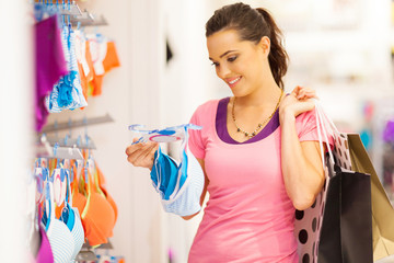 attractive young woman shopping for underwear in clothing store