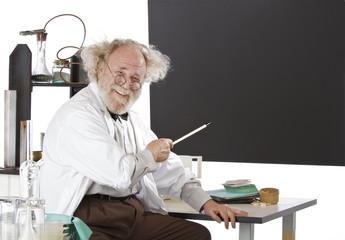 Smiling eccentric  scientist points to blackboard