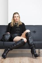 Kobieta ma na sobie czarne ubrania i buty siedzi na kanapie