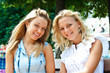 Two beautiful young woman resting on a bench in the park after s