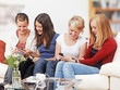 4 girls with smartphones on the sofa