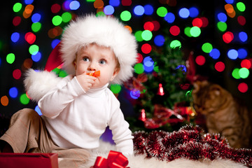funny baby in Santa Claus hat on bright festive background