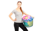 Young smiling woman holding a laundry basket full of clothes