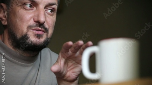 Adult Man in Pensive Mood Drinks Cup of Coffee