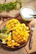 Aufgeschnittene Mango mit Limette und Zucker